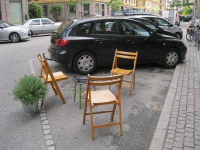 A potted lavender is the magic ingredient that transforms this table and chairs placed in an on-street parking spot into a simple, but effective, parklet.