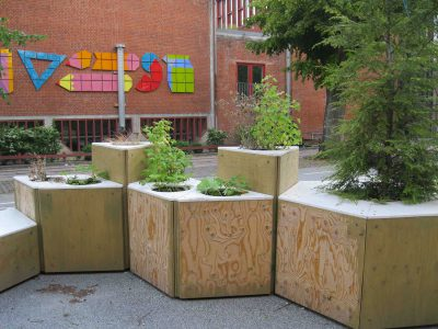 Angular, stacked plywood planters calm traffic to give priority to pedestrians and cyclists on a public street in Copenhagen.