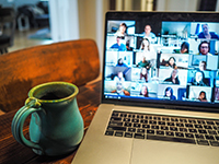 Photograph of webinar on a laptop and a cup of coffee